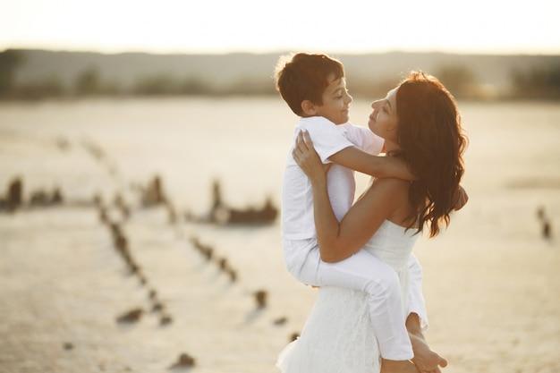 Moeder en zoon zijn gekleed in witte casual kleding en kijken elkaar aan op de zonsondergang