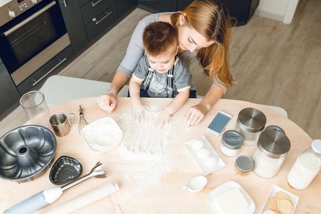 Moeder en zoon zitten achter de keukentafel met keukenspullen erop. .