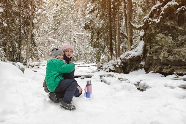 Moeder en zoon zitten en knuffelen op besneeuwde bossen.