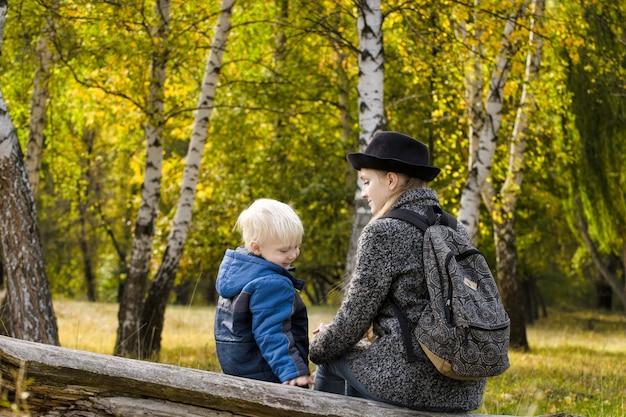 Moeder en zoon zitten in de herfst bos op een logboek.