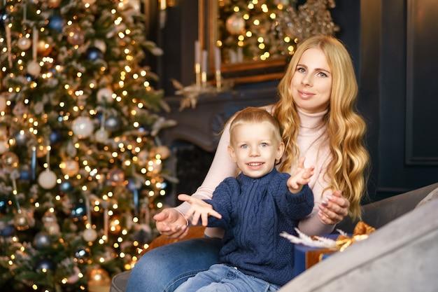 Moeder en zoon zitten in de pose van een kerstboom, vakantie concept.