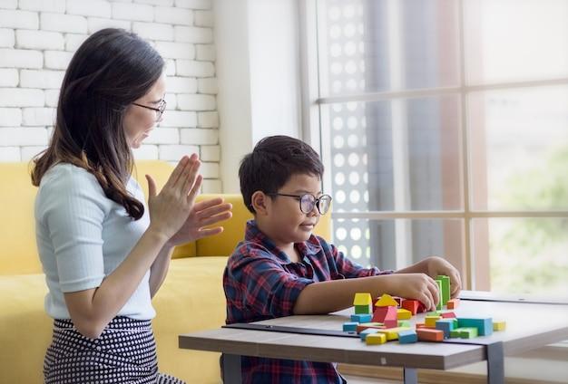 Moeder en zoon zitten in een speelkamer, spelen houten blok spel en genieten van hun tijd samen.