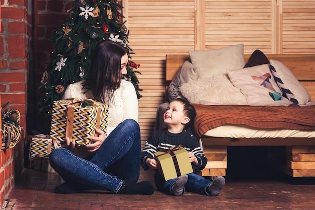 Moeder en zoon zitten op de grond en houden kerstcadeautjes vast.
