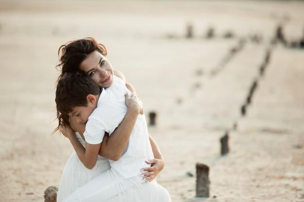 Moeder en zoon zitten op het zand en knuffelen, gekleed in witte kleren, zoon met gesloten ogen, moeder kijkt recht