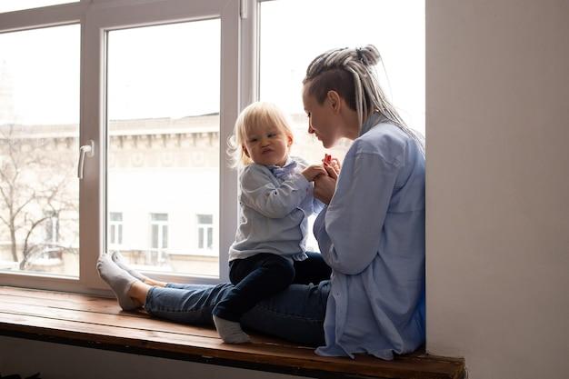 Moeder en zoon zittend op de vensterbank in de buurt van venster