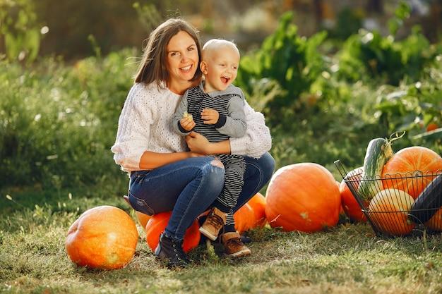 Moeder en zoon zittend op een tuin in de buurt van veel pompoenen