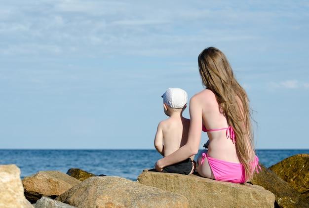 Moeder en zoon zittend op rots aan de kust en op zoek in de verte