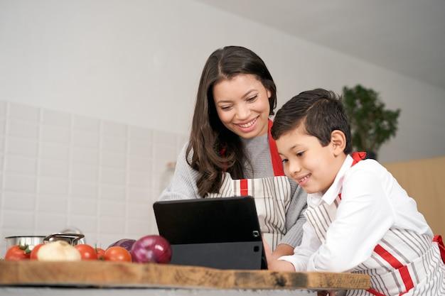 Moeder en zoon zoeken op internet naar recepten voor gezonde voeding terwijl ze groenten koken in de ...