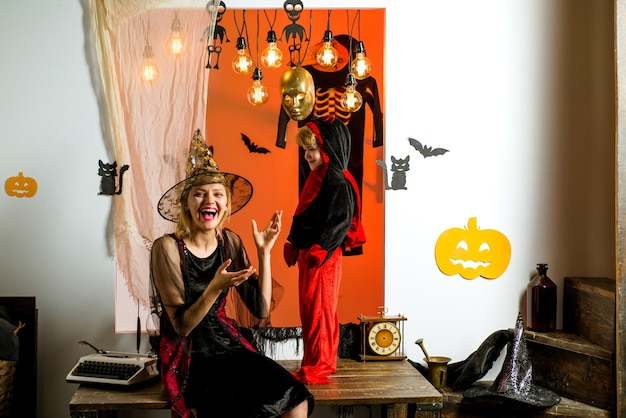 Moeder en zoonsvogelverschrikkers op halloween-achtergrond. 31 oktober. magische hoed. beste ideeën voor halloween. leuke gelukkige kleine duivel en zijn jonge moedertovenaar. halloween-concept van de familie.