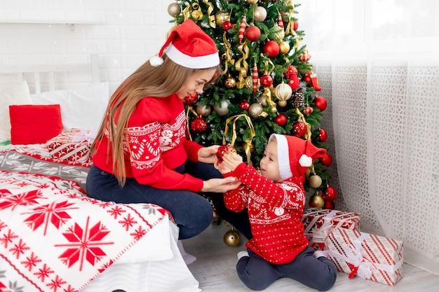 Moeder en zoontje in een rode trui en hoeden versieren de kerstboom met ballonnen in de buurt van het bed thuis en verheugen zich in het nieuwe jaar en kerstmis