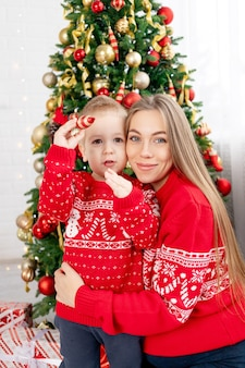 Moeder en zoontje in een rode trui onder de kerstboom thuis genieten van het nieuwe jaar en kerstmis knuffelen en feliciteren elkaar