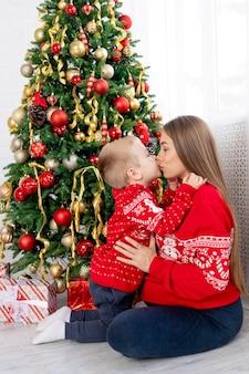Moeder en zoontje in een rode trui onder de kerstboom thuis genieten van het nieuwe jaar en kerstmis, kussen en feliciteren elkaar