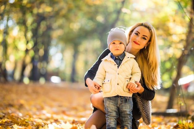 Moeder en zoontje in park of bos, buitenshuis. samen knuffelen en plezier maken in het herfstpark