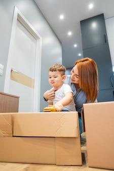Moeder en zoontje spelen met speelgoed in huis