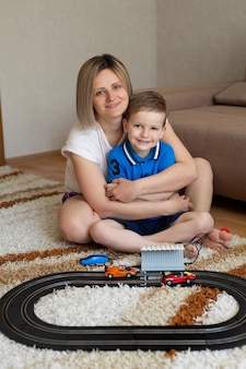 Moeder en zoontje spelen thuis racen op het tapijt, hebben plezier en knuffelen.