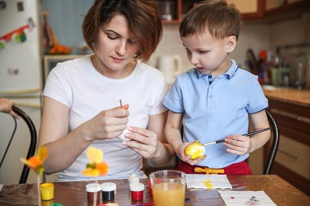 Moeder en zoontje versieren paaseieren thuis aan de keukentafel
