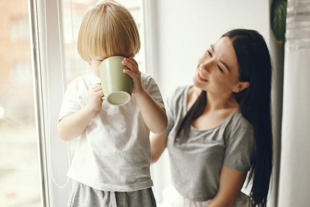 Moeder en zoontje zittend op een vensterbank met een thee