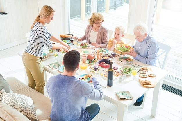 Moeder eten serveren tijdens familiediner