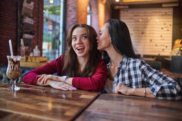Moeder fluistert roddelen en vertelt een geheim aan haar jonge verrast dochter in het oor in een coffeeshop