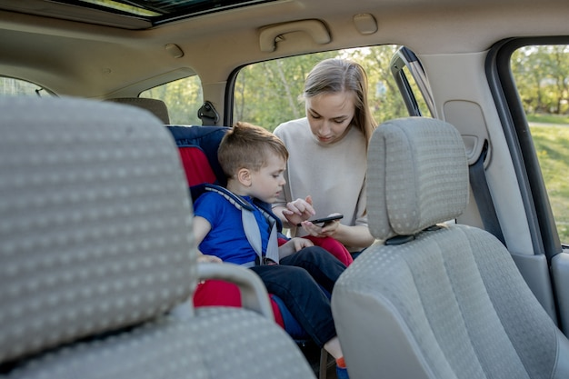 Moeder geeft de telefoon jongetje zit in een autostoeltje. veiligheid van het vervoer van kinderen