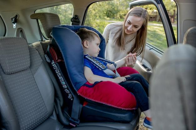 Moeder geeft de telefoon kleine jongen zittend in een autostoeltje. veiligheid van vervoer van kinderen.