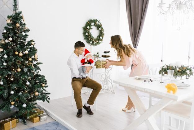 Moeder geeft een kerstcadeau aan papa en zijn zoontje in de buurt van de kerstboom.