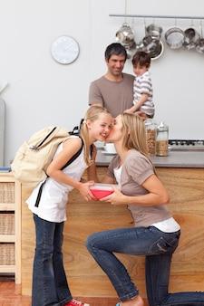 Moeder geeft haar dochter de lunch op school en een kus
