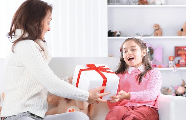 Moeder geeft haar dochter een doos met een verjaardagscadeau.