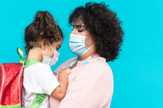 Moeder geeft haar dochtertje een knuffel voordat ze weer naar school gaat