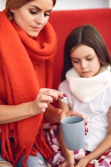 Moeder geeft haar zieke dochter hete thee