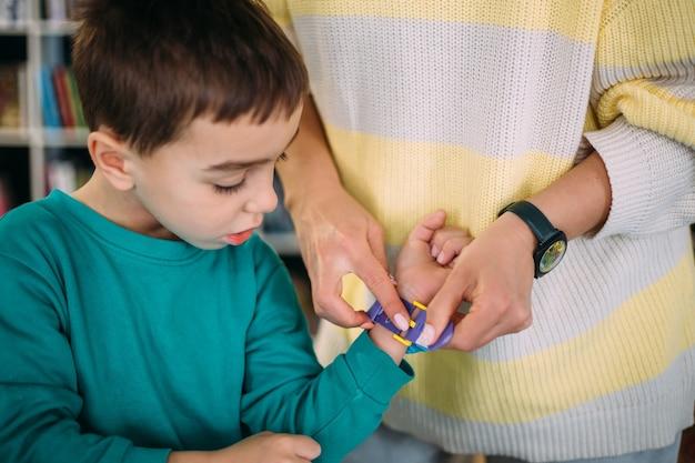 Moeder geeft haar zoon zijn eerste horloge en leert de tijd op de klok te bepalen