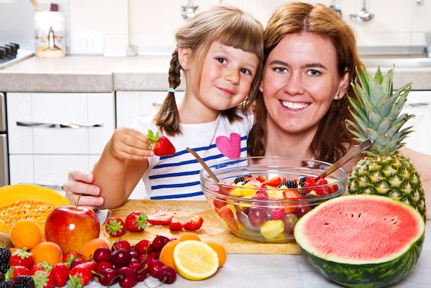 Moeder geeft het kleine meisje een fruitsalade in de keuken.
