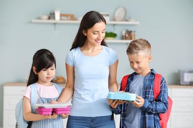 Moeder geeft lunchboxen aan haar kleine kinderen voordat ze naar school gaan
