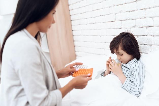 Moeder geeft medicijnen aan een zieke zoon thuis.
