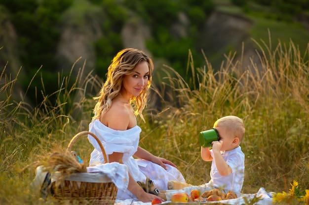 Moeder geeft melk aan haar zoon. mam geeft de baby te eten. moeder met haar zoon in de natuur. de zoon drinkt melk. ouderlijke zorg voor kinderen. kinderdag. dag van de bescherming van kinderen.