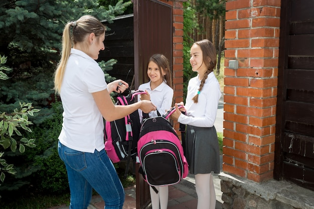 Moeder geeft rugzakken aan haar dochters die 's ochtends naar school gaan