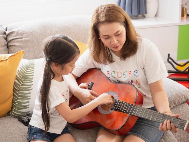 Moeder gitaarspelen met dochter in de kamer
