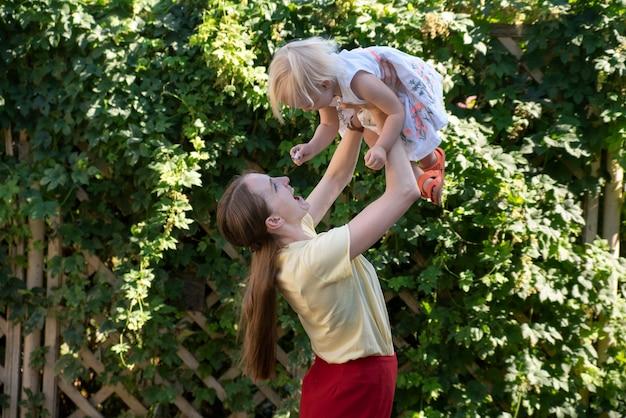 Moeder gooit de baby in de lucht. moeder omcirkelt kind in haar armen. portret van gelukkige mama en kind.