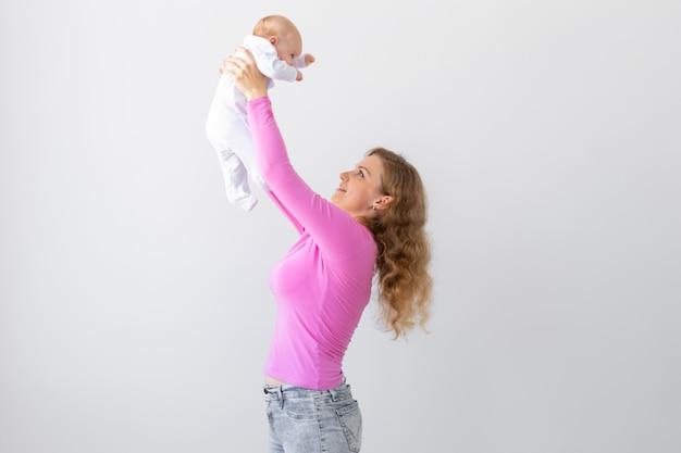 Moeder gooit de baby over, lacht en speelt met hem
