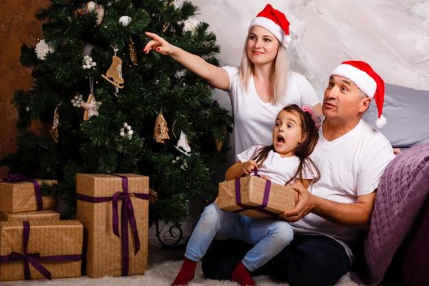 Moeder, grootvader en verraste kleindochter in de buurt van de kerstboom