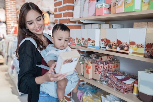 Moeder haalt wat product op in babywinkel terwijl ze haar zoon draagt