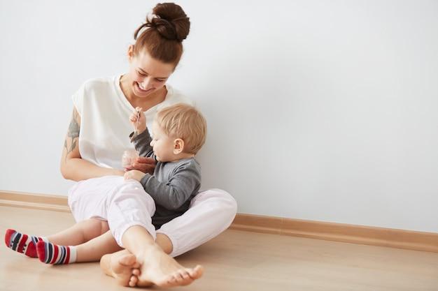 Moeder haar babyjongen voeden met lepel