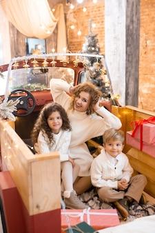 Moeder haar kleine kinderen knuffelen op kerstvakantie, met lichten in rode auto pick-up trailer