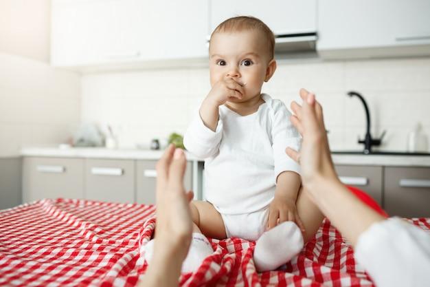 Moeder handen bereiken haar schattige baby zittend op het bureau