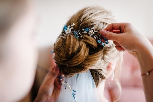 Moeder handen met ornamenten en dressing sluier bruid. bruidsmeisje bruid voorbereiden, sluier helpen vastmaken. klaar maken. bruiloft concept voorbereidingen.