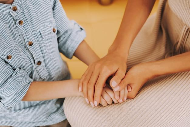 Moeder handen troost kleine jongen bij kliniek