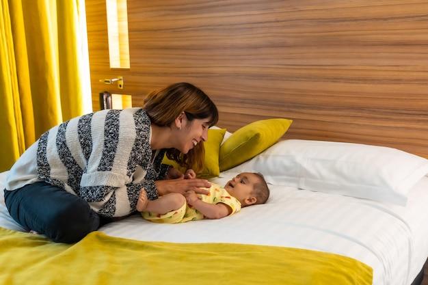 Moeder heeft plezier met haar baby op het bed in haar slaapkamer, jonge blanke eerste keer met haar vier maanden oude baby