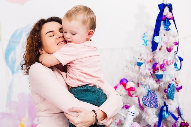 Moeder heeft plezier met haar zoon, zittend in de kamer, gekleed voor kerstmis en nieuwjaar