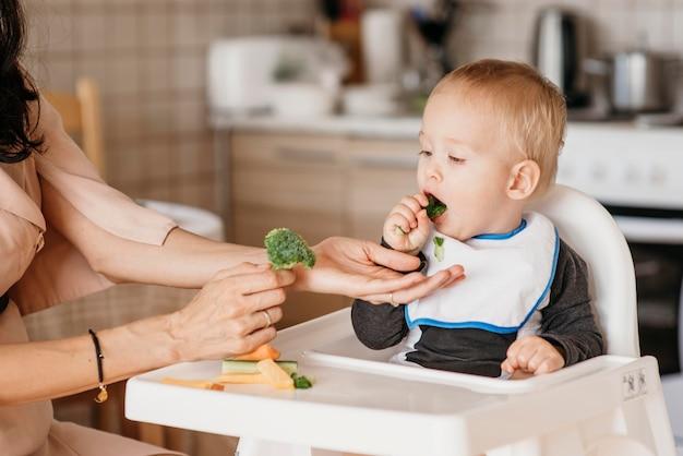 Moeder helpt baby om te kiezen welk voedsel hij wil eten