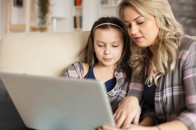 Moeder helpt dochtertje te typen op het toetsenbord van de laptop zittend op de bank in de woonkamer.